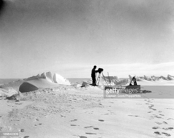 Herbert Ponting photographing an ice crack at Cape Evans photographed during the last tragic voyage to Antarctica by Captain Robert Falcon Scott on...