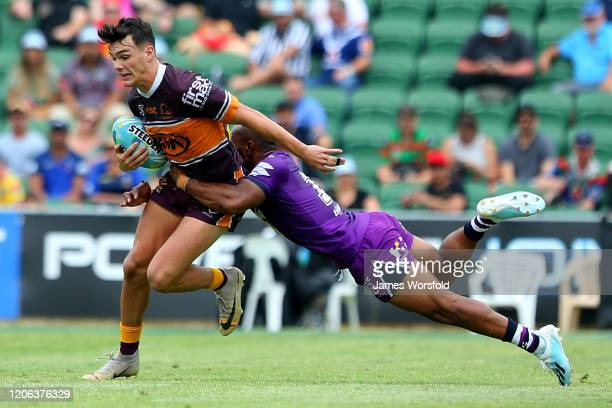 Herbie Farnworth of the Broncos tries to escape the diving tackle of Justin Olam of the Storm during the match between the Broncos and Storm from Day...