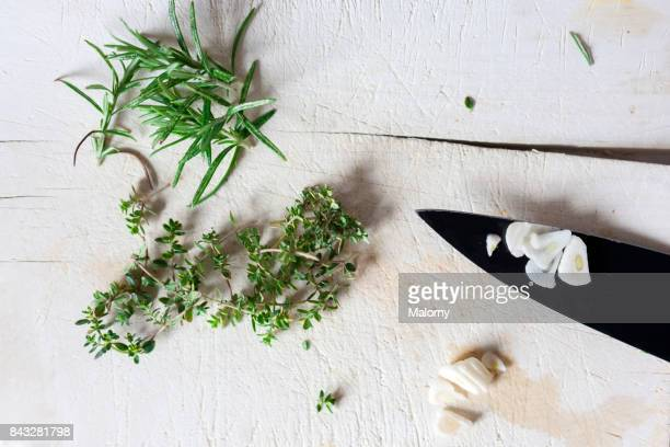 Herbs and Garlic on white cutting board with black knife