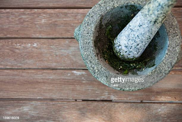 Herbs being ground in pestle and mortar