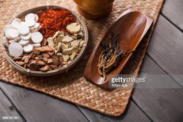 Herbs, spices and chopped roots lying on wicker coaster