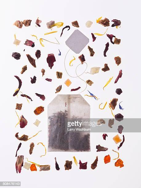 Herbs with tea bag over white background