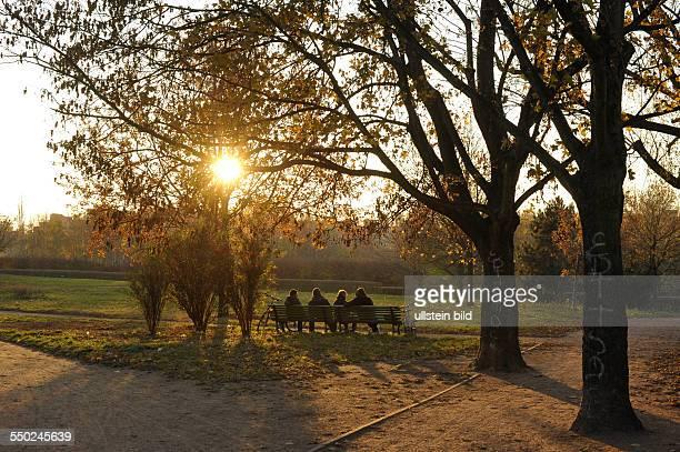Herbst in Berlin Besucher genießen die letzten Sonnenstrahlen auf einer Parkbank im Mauerpark in BerlinPrenzlauer Berg