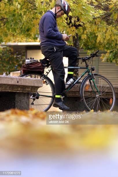 Herbst in Berlin Fahrradfahrer am Gendarmenmarkt Deutscher und Franzoesischer Französischer Dom Schauspielhaus Konzerthaus Spiegelung