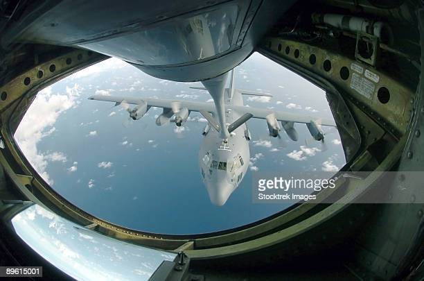 A C-130 Hercules is refueled by a KC-135 Stratotanker, over the Pacific Ocean.