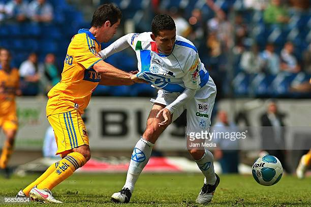 Herculez Gomez of Puebla vies for the ball with Antonio Castro of Tigres during a match as part of the 2010 Bicentenary Tournament in the Mexican...
