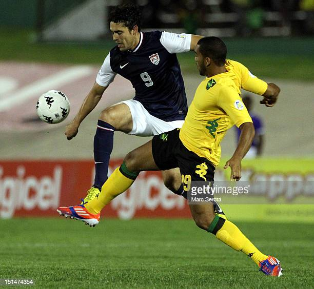 Herculez Gomez of the united States battles for the ball with Adrian Mariappa of Jamaica at National Stadium on September 7 2012 in Kingston Jamaica
