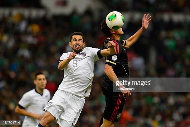 Herculez Gomez of the United States fights for the ball with Hector Moreno of Mexico during a match between Mexico and USA as part of the CONCACAF...