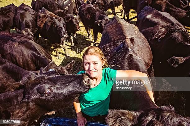 Herd of Black Angus Cattle Surrounding Female Rancher