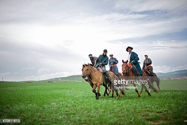 Herders attending a Naadam festival in Ugtaal Soum trot by on horseback Mongolian pastoral herders make up one of the world's largest remaining...