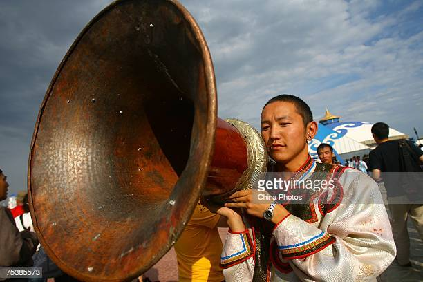 A herdman carries a giant clarion during world's tallest man Bao Xishun's traditional Mongolian wedding ceremony at Genghis Khan's Mausoleum on July...