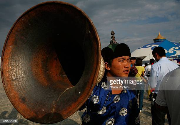 A herdsman carries a giant clarion during world's tallest man Bao Xishun's traditional Mongolian wedding ceremony at Genghis Khan's Mausoleum on July...