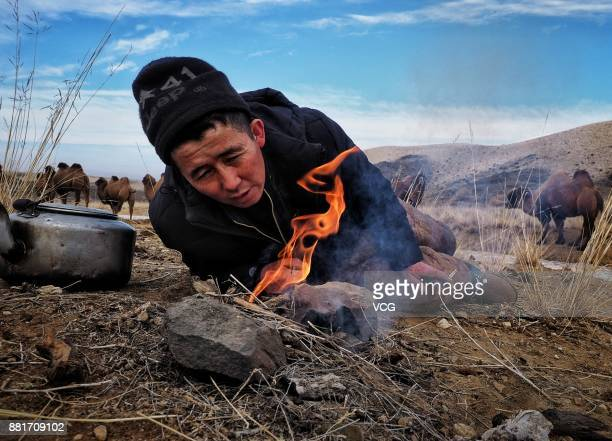 A herdsman lights a fire to melt ice for water during the winter migration on November 28 2017 in Altay Xinjiang Uyghur Autonomous Region of China...