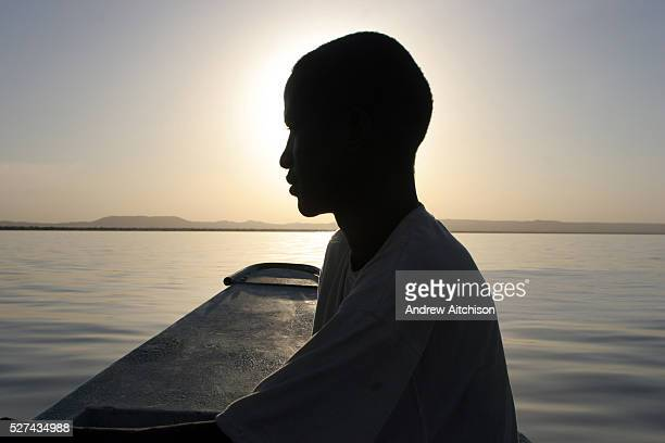 A herdsman travels across the lake on a boat The Turkana herdsmen have had to change their traditional way of living as pastoralists and learn new...