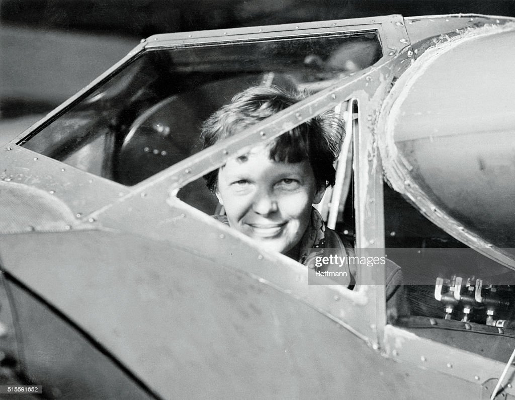 Amelia Earhart Peering out from Airplane : News Photo