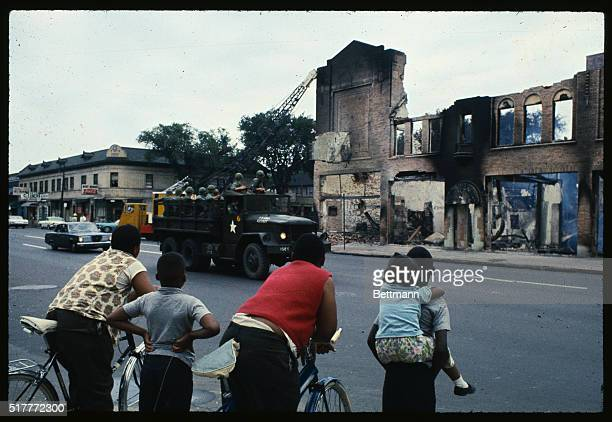 Here the gutted remains of buildings attest to the destruction caused by two days of rioting in Detroit's west side Four children on bikes watch from...