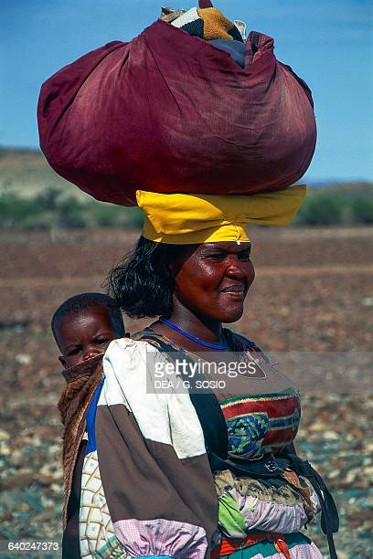 Herero woman with a bag on her head and a child strapped on her back Damaraland Wilderness Area Namibia
