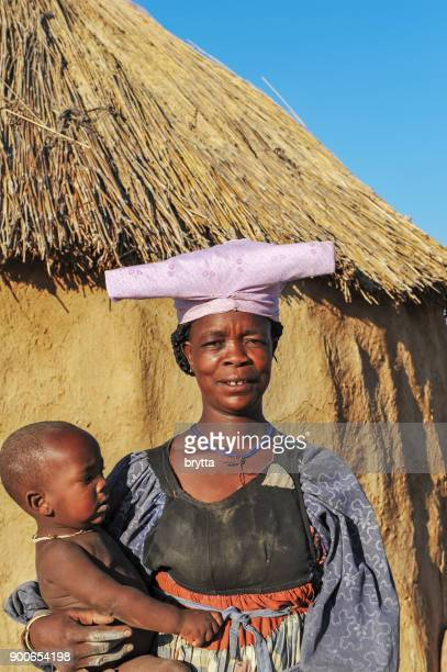 herero women with baby in her arms - opuwo tribe stock photos and pictures