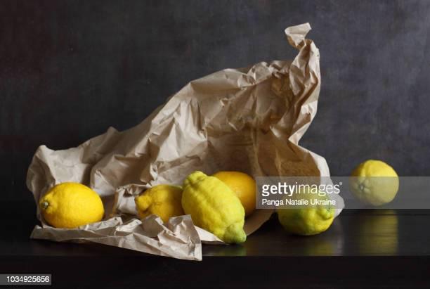 heritage lemons wrapped in crumpled paper - naturaleza muerta fotografías e imágenes de stock