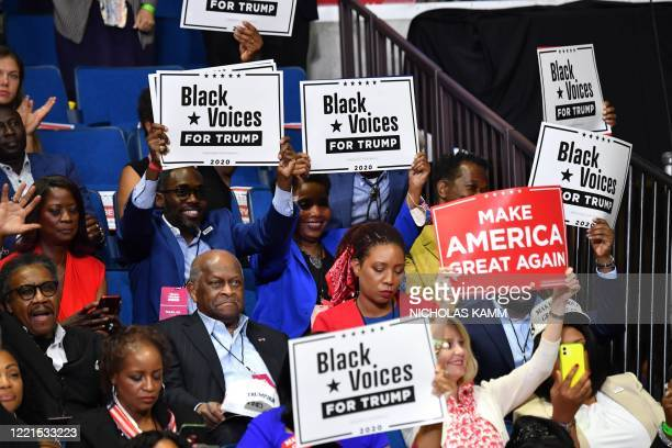 Herman Cain and supporters of US President Donald Trump Black Voices listen to him speak during a campaign rally at the BOK Center on June 20 2020 in...