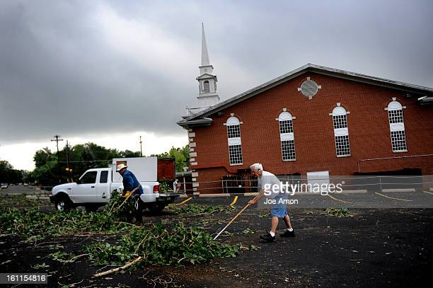 Herman Pflueger carries limbs as maintenance man Ray Bond sweeps the parking lot of the Center Point Community Church in Arvada I came early to...