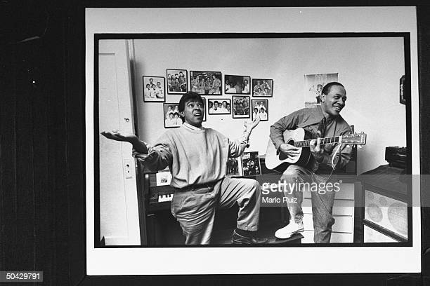 Herman Santiago singing w outstretched arms while Jimmy Merchant accompanies him on guitar in his apt a federal jury recently ruled that Santiago and...