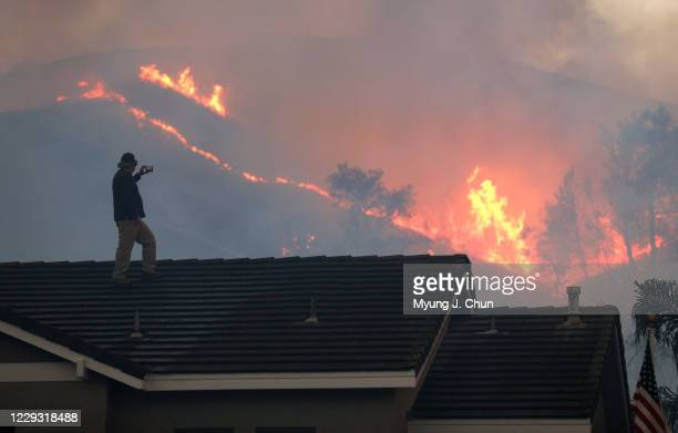 Herman Termeer watches the brushfire at Chino Hills State Park from the roof of his house on Tuesday, Oct. 27, 2020 in Chino Hills, CA.