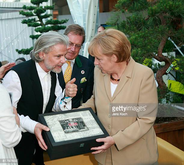 Hermann Buehlbecker hands over a box of cookies of his company Lambertz to Angela Merkel attend the CHIO Media Night on July 1 2008 in Aachen Germany...