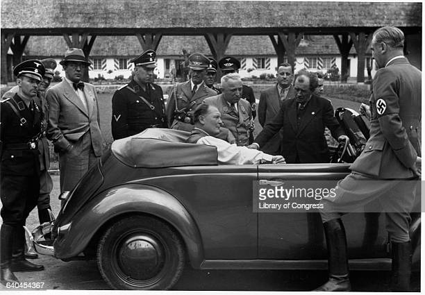 Hermann Goering sits in the backseat of a Volkswagen convertible at Carinhall hunting lodge surrounded by Nazi officials