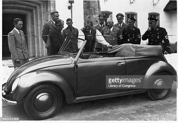 Hermann Goering stands next to a Volkswagen convertible at Carinhall hunting lodge with Robert Ley and Ferdinand Porsche
