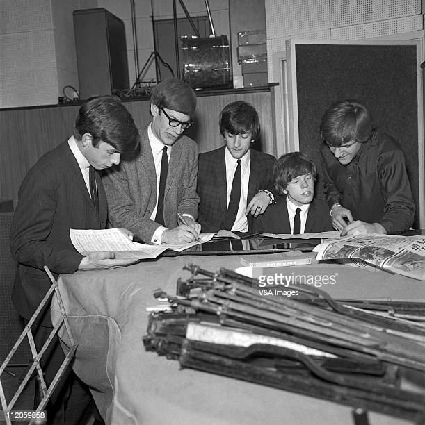 Herman's Hermits Barry Whitwam Derek Leckenby Keith Hopwood Peter Noone Karl Green posed group shot around a piano in a recording studio 1964
