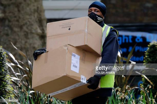 Hermes delivery courier carries boxes as he makes a delivery to 10 Downing Street, the official residence of Britain's Prime Minister, in central...