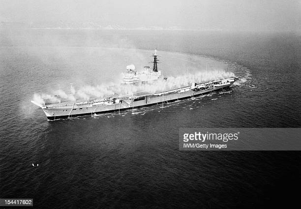 HMS Hermes During 'PreWetting' June 1961 Aerial Photograph HMS HERMES with its array of water jets spraying in a Prewetting operation The system of...