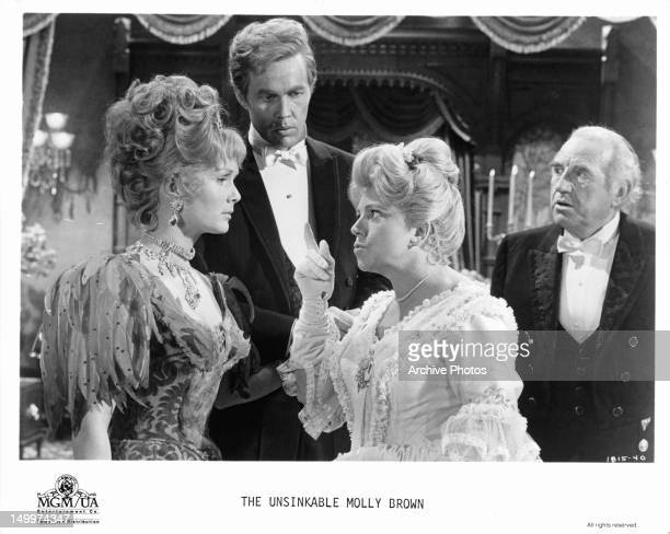 Hermione Baddeley pointing her finger at Debbie Reynolds as Harve Presnell and Ed Begley watch in a scene from the film 'The Unsinkable Molly Brown'...
