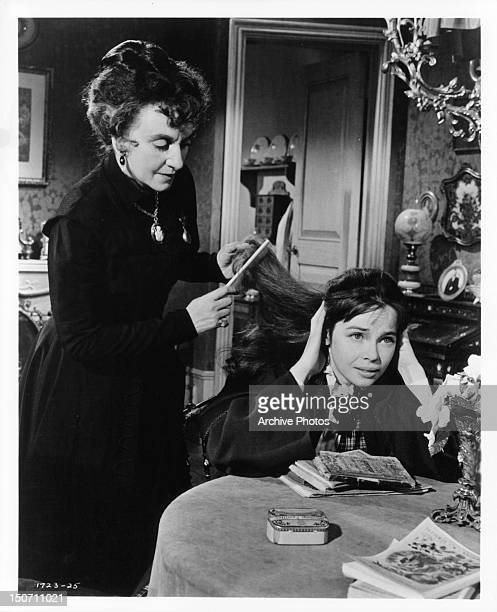 Hermione Gingold brushing the hair of Leslie Caron in a scene from the film 'Gigi' 1958