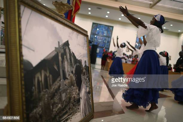 Hermonde Alcenat takes part in a dance near a framed picture of a church that was destroyed by the massive 2010 Earthquake in Haiti during a service...