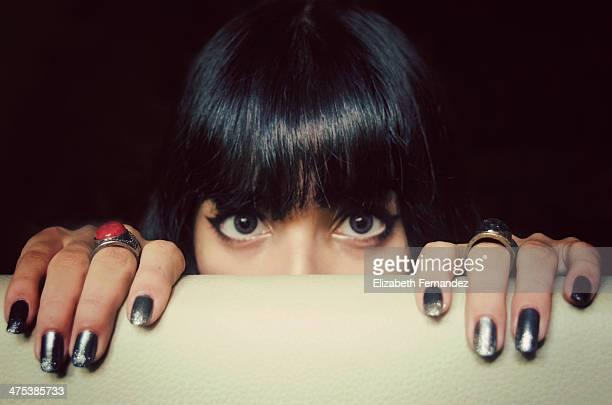 Hermosa joven mujer asomada tras una pared