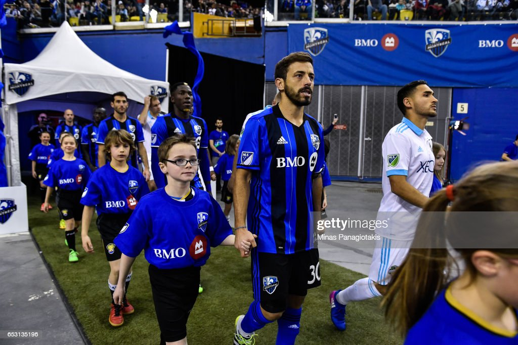 Hernan Bernardello #30 of the Montreal Impact is escorted to the field by a child during the MLS game against the Seattle Sounders FC at Olympic Stadium on March 11, 2017 in Montreal, Quebec, Canada. The Seattle Sounders FC and the Montreal Impact end up in a 2-2 draw.