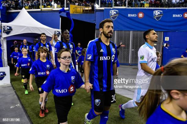 Hernan Bernardello of the Montreal Impact is escorted to the field by a child during the MLS game against the Seattle Sounders FC at Olympic Stadium...
