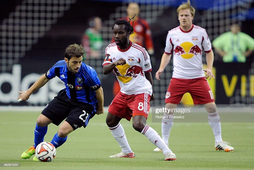 Hernan Bernardello #23 of the Montreal Impact runs with the ball in front of Peguy Luyindula #8 of the New York RedBulls during the MLS game at the Olympic Stadium on April 5, 2014 in Montreal, Quebec, Canada.