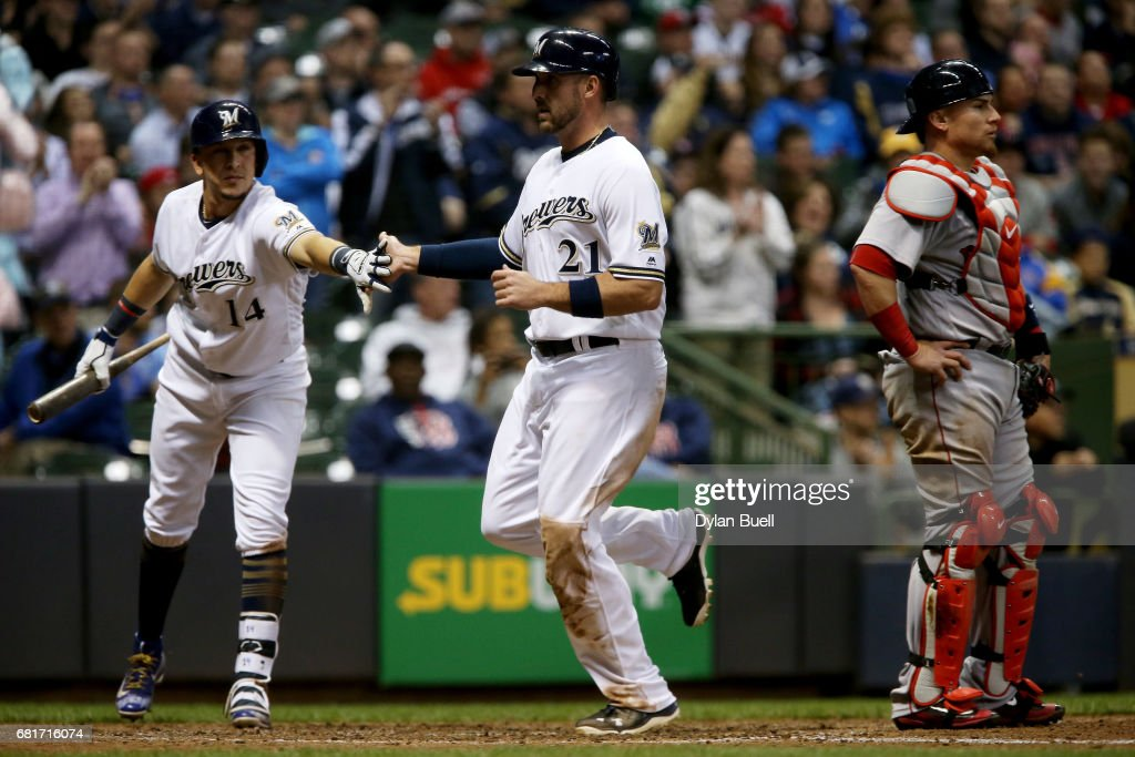 Hernan Perez #14 and Travis Shaw #21 of the Milwaukee Brewers celebrate after Shaw scored a run past Christian Vazquez #7 of the Boston Red Sox in the fifth inning at Miller Park on May 10, 2017 in Milwaukee, Wisconsin.