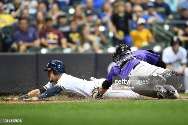 Hernan Perez of the Milwaukee Brewers beats a tag at home by Chris Iannetta of the Colorado Rockies during the sixth inning of a game at Miller Park...