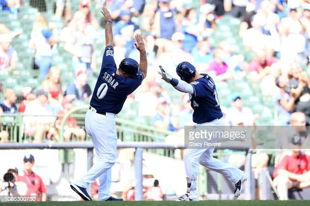 Hernan Perez of the Milwaukee Brewers celebrates a home run with third base coach Ed Sedar during the ninth inning of a game against the Washington...