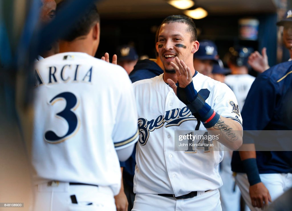 Hernan Perez #14 of the Milwaukee Brewers is greeted by Orlando Arcia #3 in the dugout after scoring in the first inning during their game against Miami Marlins at Miller Park on September 16, 2017 in Milwaukee, Wisconsin.