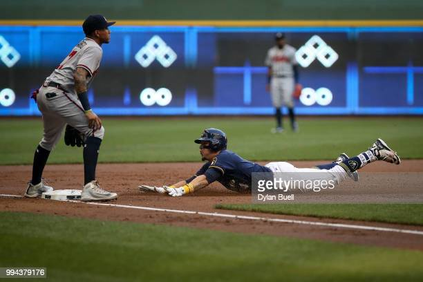 Hernan Perez of the Milwaukee Brewers slides into third base for a triple past Johan Camargo of the Atlanta Braves in the second inning at Miller...