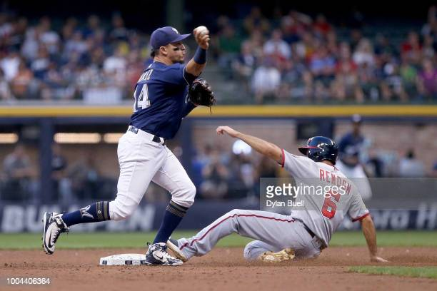 Hernan Perez of the Milwaukee Brewers throws to first base past Anthony Rendon of the Washington Nationals in the second inning at Miller Park on...