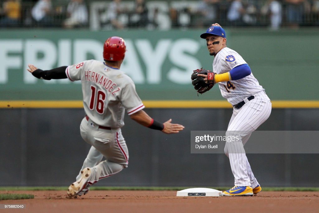 Hernan Perez #14 of the Milwaukee Brewers turns a double play past Cesar Hernandez #16 of the Philadelphia Phillies in the first inning at Miller Park on June 15, 2018 in Milwaukee, Wisconsin.