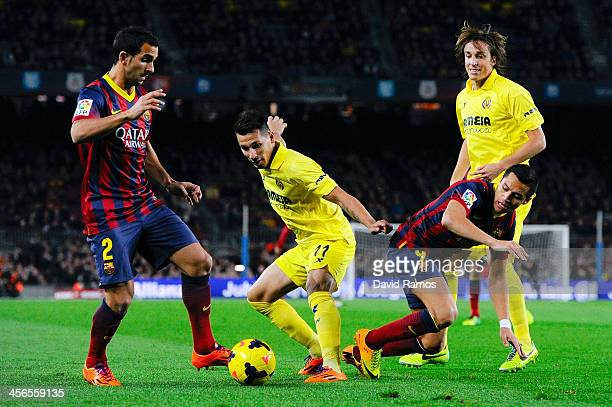 Hernan Perez of Villarreal CF duels for the ball with Martin Montoya and Alexis Sanchez of FC Barcelona during the La Liga match between FC Barcelona...