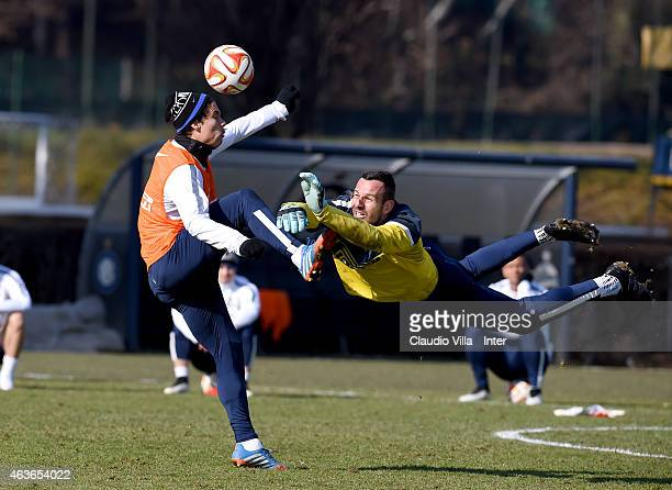 Hernanes and Samir Handanovic compete for the ball during a FC Internazionale training session at the club's training ground at Appiano Gentile on...