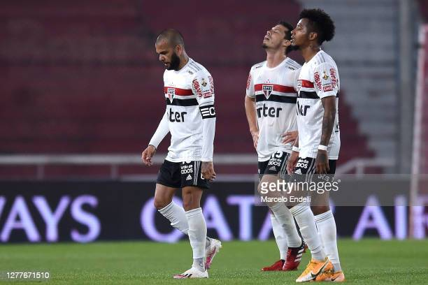 Hernanes, Dani Alves and Tche Tche of Sao Paulo react at the end of the first half during a Copa CONMEBOL Libertadores 2020 group D match between...